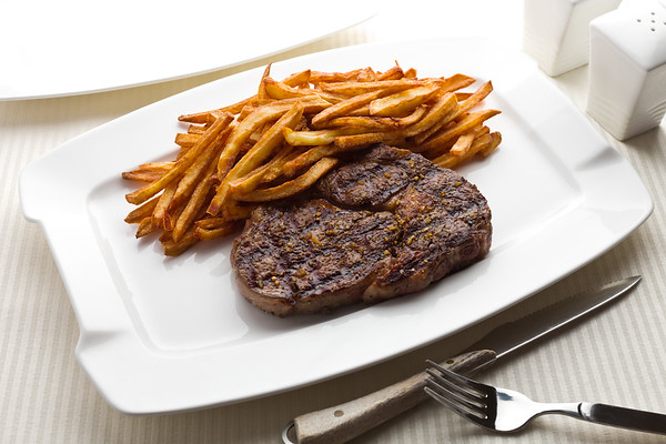 Steak frite (french frie)  in a white plate.