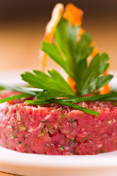 Loin beef tartar on a white plate with parsley on the top. Very shallow depth of field.Focus on the front of the meat.