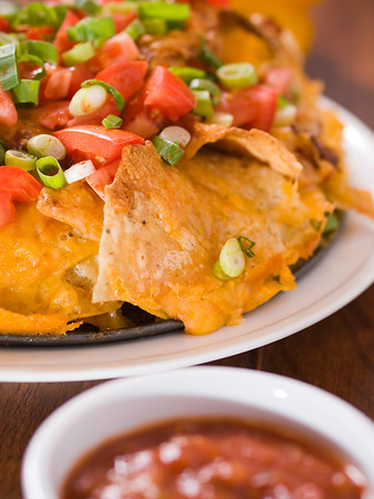 nachos with salsa  in the foreground.Shallow depth of field.