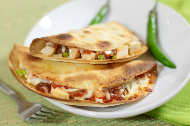 Quesadillas meal made with chicken meat, salsa sauce and melted cheese. Grilled pita and green background. Very shallow depth of field.