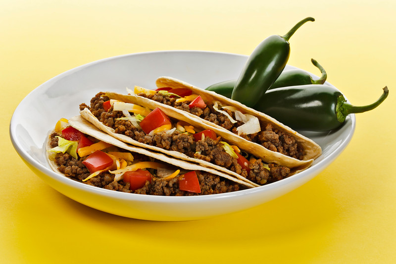 Taco wrap with beef meat in a white plate. Green hot pepper on the side. Yellow background.