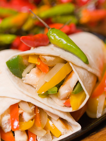 fajitas chicken on iron cooking plate with red and green hot pepper in the background. Shallow depth of field.