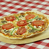 fresh cooked pizza on a wooden plate. Checkered red nap. Shallow depth of field.