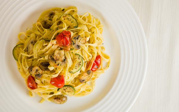 Vegetarian tagliatelle pasta with mushroom,zukini,cucumber, tomato and pesto sauce. Very shallow depth of field.