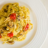 Vegetarian tagliatelle pasta with mushroom,zukini,cucumber, tomato and pesto sauce. Very shallow depth of field.