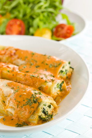 Pasta cannelloni with spinach and ricotta. Rosa sauce on it with melted mozzarella cheese. Salad in the background.<br /> <br /> Concept : healthy eating and meal time<br /> Orientation : vertical