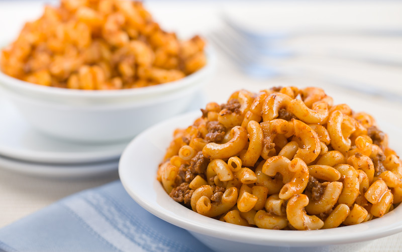 Macaroni with tomato meat sauce. Blue background. Shallow depth of field.
