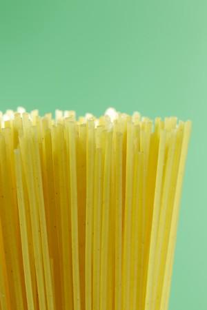 uncooked macro spaghetti pasta on a green background.