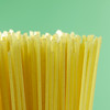 uncooked macro spaghetti pasta on a green background.