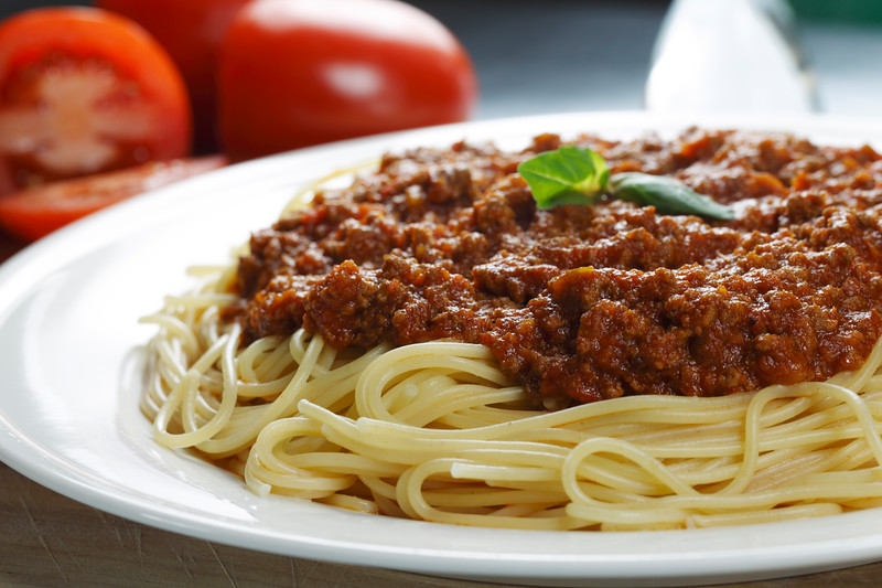 spaghetti meal on a white plate with meat sauce. Shallow depth of field.
