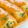 Pasta cannelloni with spinach and ricotta. Rosa sauce on it with melted mozzarella cheese. <br /> <br /> Concept : healthy eating and meal time<br /> Orientation : vertical