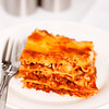Fresh portion lasagna on a plate with a white background. Very shallow depth of field.