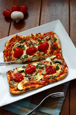vegetarian pizza on a white plate with fork and knife utensil.