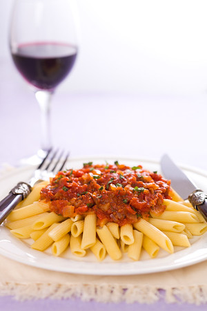 Arrabbiata tomato sauce with penne pasta in a white plate. Very shallow depth of field. Focus on the sauce.