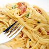 Fettuccini carbonara pasta with a fork on a white plate. Shallow depth of field.