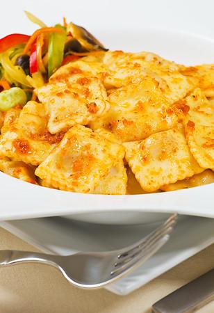 Ravioli pasta in a white plate with tomato sauce.