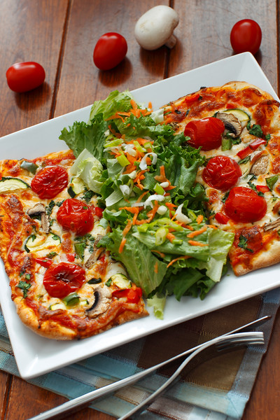 vegetarian pizza on a white plate with green salad on the side.