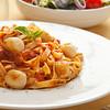 Tagliatelle pasta with scallop and tomato sauce.