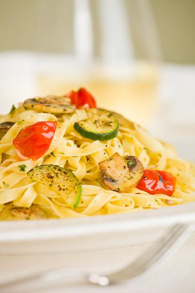 Vegetarian tagliatelle pasta with mushroom,zukini,cucumber, tomato and pesto sauce. White wine and green background. Very shallow depth of field.