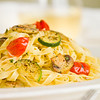 Vegetarian tagliatelle pasta with mushroom,zukini,cucumber, tomato and pesto sauce. White wine and green background. Very shallow depth of field.
