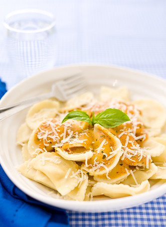 Agnolotti pasta with tomato rosa sauce on a beautiful blue tablecloth. Very shallow depth of field.