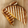 grilled cheese sandwich on a wooden board. Shallow depth of field.