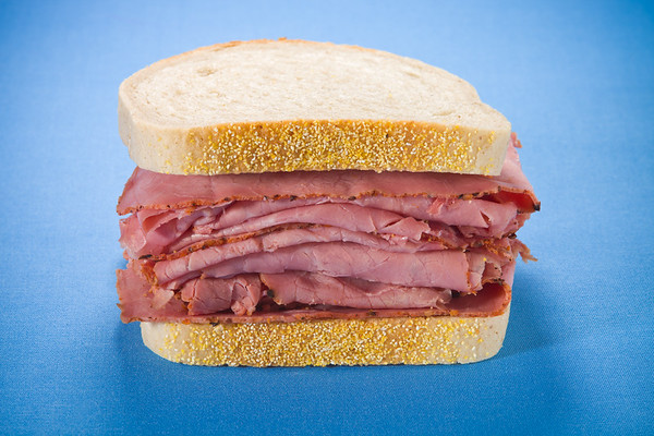 Smoked meat  beef sandwich on a blue background.