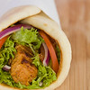 Gyros pita sandwich with chicken souvlaki meat and vegetable. Very shallow depth of field.