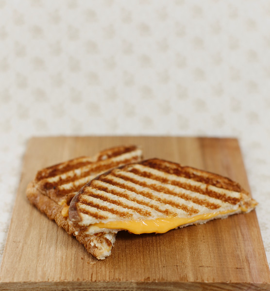 grilled cheese sandwich on a wooden board and a brown background.Lot of space to add text. Shallow depth of field.
