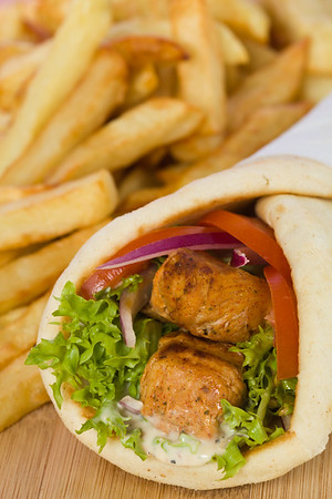 Gyros pita sandwich with chicken souvlaki meat and vegetable. French fries in the background. Very shallow depth of field.