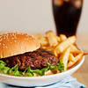 hamburger with french fries on a white plate with cola drink in the background. Shallow depth of field.
