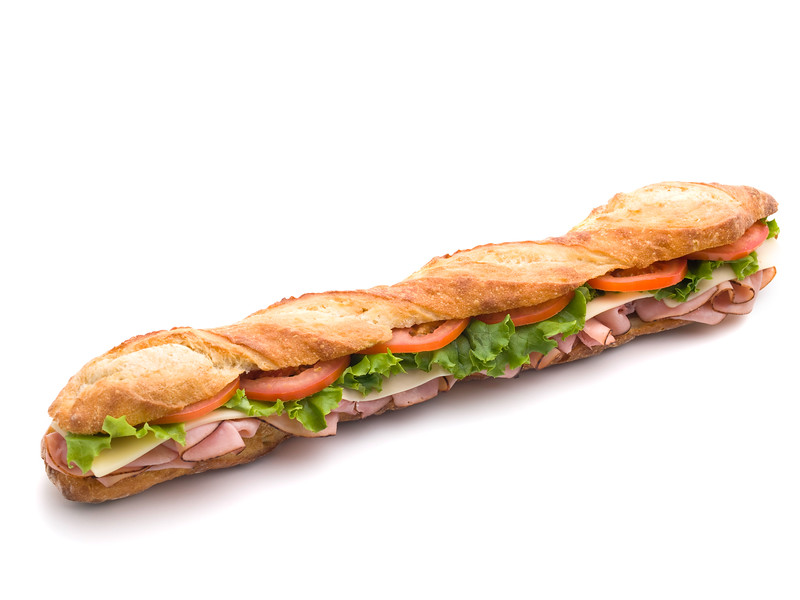 fresh submarine sandwich with ham,tomato,cheese and salad on a white background