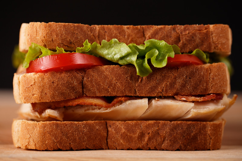 chicken club sandwich on a wooden cutting board with very shallow depth of field.