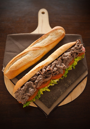 Beef meat sandwich with baguette bread on the side. Very shallow depth of field.