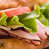 fresh macro submarine sandwich with ham,tomato,cheese and salad. Shallow depth of field