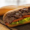 Beef sandwich with tomato and salad on a table. Very shallow depth of field.