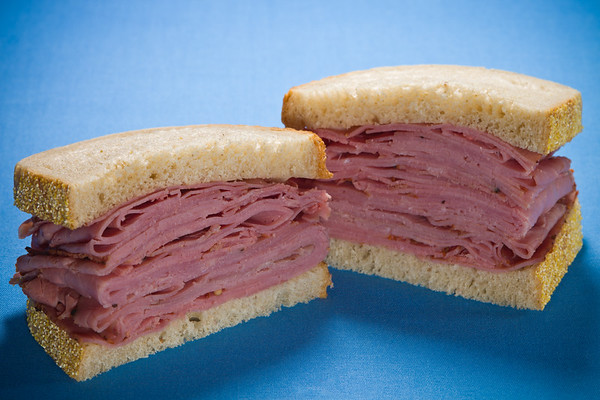 Sliced smoked meat  beef sandwich on a blue background.