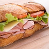 fresh submarine sandwich with ham,tomato,cheese and salad on a wooden board