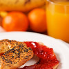 fresh handmade bagel for the breakfast with fruit and juice in the background. Very shallow depth of field.
