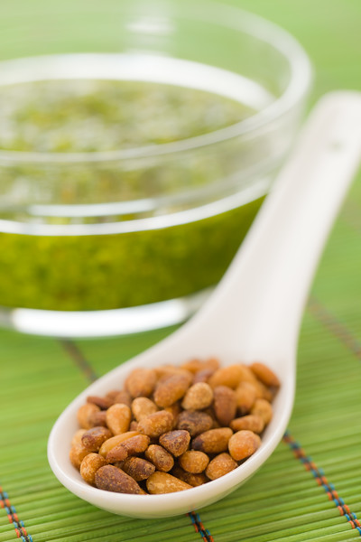 Pine nuts in a spoon with pesto sauce in the background. Extreme shallow depth of field.
