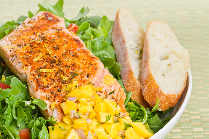 Grilled atlantic salmon fish on salad. Fruit salsa on the side. Very sharp.