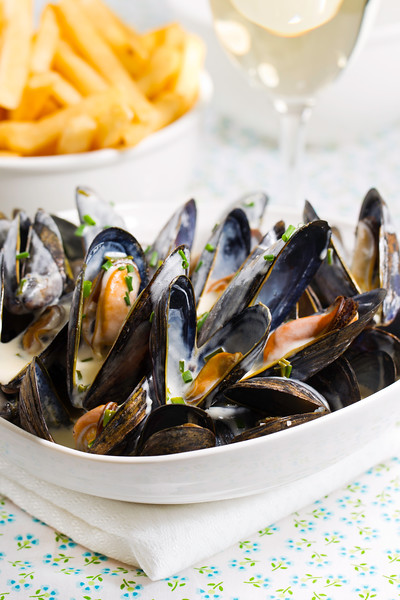 Mussel with white wine sauce and french frie  on a plate. Very shallow depth of field.
