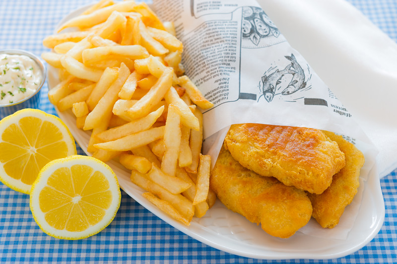 English fish and chips meal with mayonaise sauce and french fries on the side. Shallow depth of field.