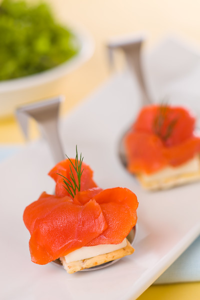 Appetizer smoked salmon with cream cheese and salad in the background. Very shallow depth of field.