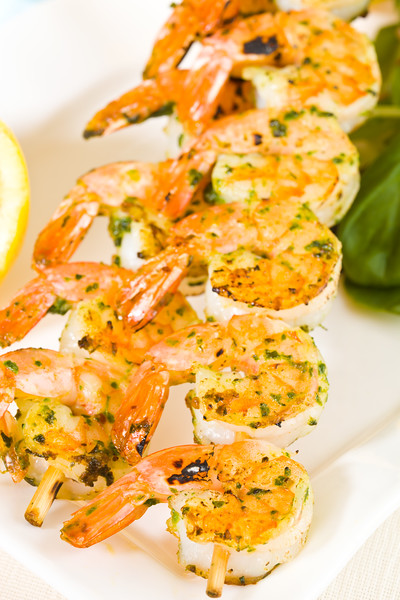Fresh shrimp skewers on a white plate. Macro photography. Very shallow depth of field.
