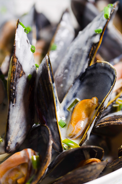 Mussel with white wine sauce  on a plate. Very shallow depth of field.