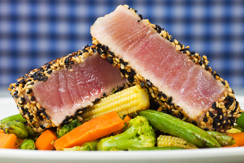 Cooked yellow tuna meal with fresh vegetable on a blue background.