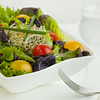 Mixed green salad meal in a white bowl with fork and glass of water, Shallow depth of field.