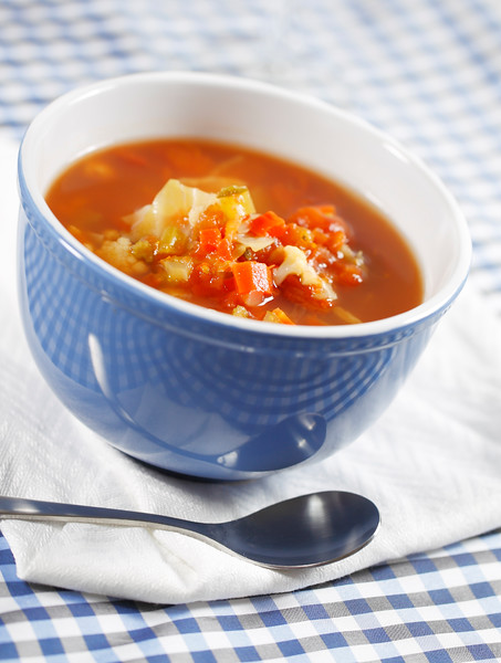 minestrone vegetable soup on a white napkin. Country style with blue checked nap and shallow depth of field.