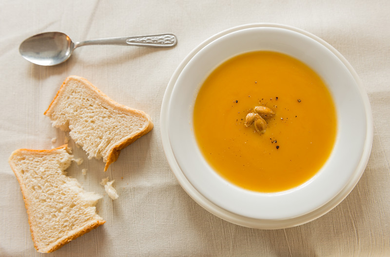 Pumpkin soup cream with spoon and a slice of bread on the side.